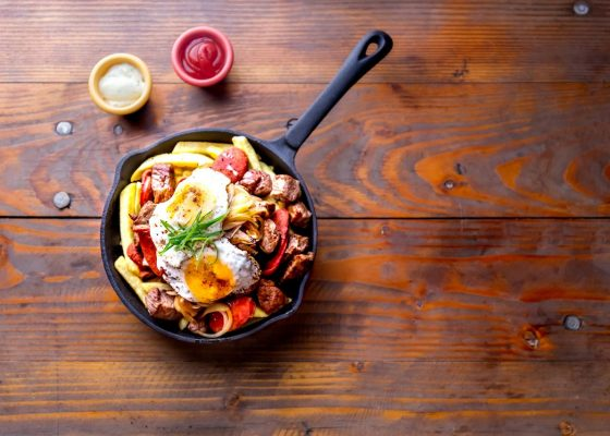 french-fries-topped-with-sliced-__beef-tipical-sausages-chorrisos-fried-onion-and-eggs-served-in-iron-cast-pan-with-sauces