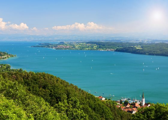 View on Lake Constance Bodensee with blue sky and the Alps in background
